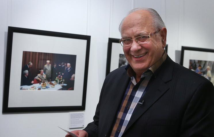 """Владимир Мусаэльян на фотовыставке ТАСС """"Вокруг меня гудит ХХ век"""" рядом с одной из своих фоторабот, 2014 год"""