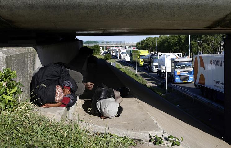 Мигранты спят вдоль автомагистрали, ведущей к порту, где на пароме можно пересечь Ла-Манш. Кале, север Франции, 24 июня 2015 года
